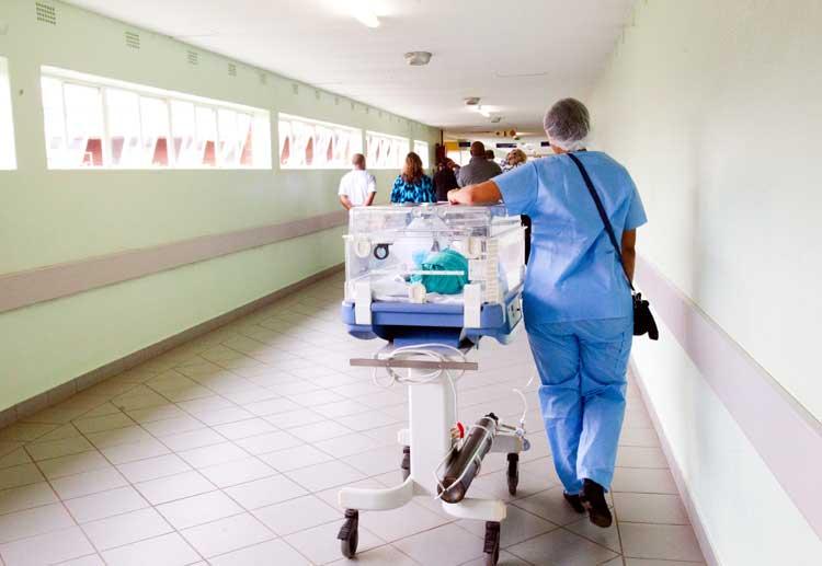 nicu baby in incubator being wheeled down hospital hall